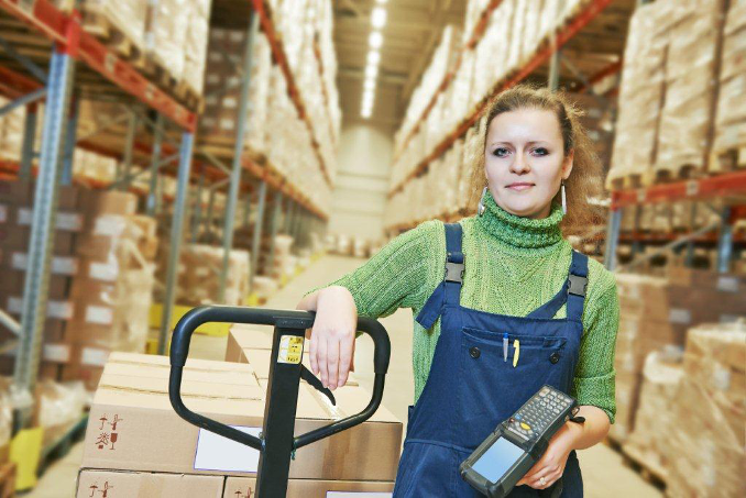 Woman with hand truck in warehouse