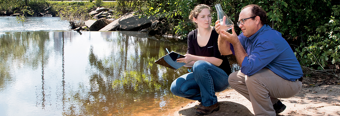 Scientists inspecting water from river in a beaker