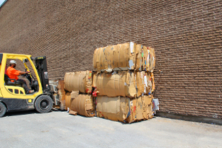 Worker moving recycled material with forklift