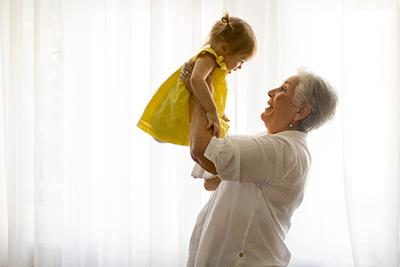 grandmother lifting baby in yellow dress